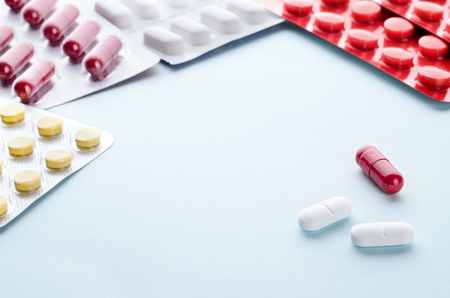 psychotropic medication: Assorted colorful pills and capsules in a Blister packaging on a light background close up, horizontal, copy space, selective focus, medical concept. Stock Photo