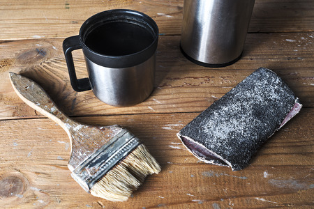 home repairs: Old brush, sandpaper and thermos on a brown tattered wooden background, joinery work, home repairs