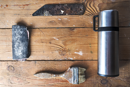 home repairs: Old brush, sandpaper, thermos and knife  for carving on a brown tattered wooden background, joinery work, home repairs Stock Photo
