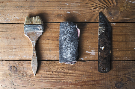 home repairs: Old brush, sandpaper and knife for carving on a brown tattered wooden background, joinery work, home repairs, top view Stock Photo