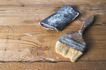 home repairs: Old brush and sandpaper on a brown tattered wooden background, joinery work, home repairs