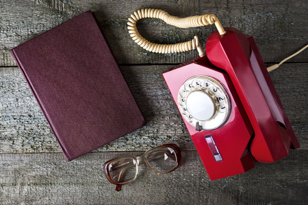 turn table: Red vintage phone, old glasses, notebook, and pencil on wooden background, close-up, top view, pick up the phone