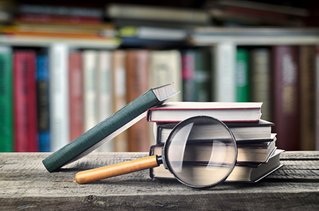 reading room: Stack of books and magnifier on wooden table with bookshelf, invitation to study literatures, close up, reading room Stock Photo