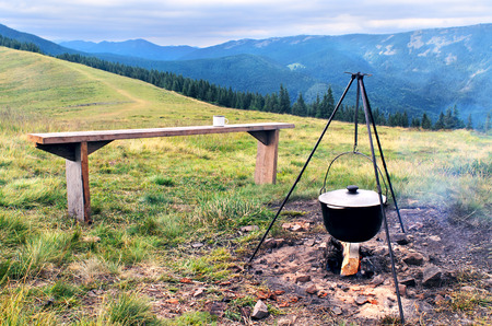 Camping fire and tourists bowler with preparing food in mountains. Cooking on a fire in field conditions. Bonfire with bowler dinner. Cooking in marching pot. Place for camping. A pot on the fire with a meal. Empty bench at the camp fire view over the mou