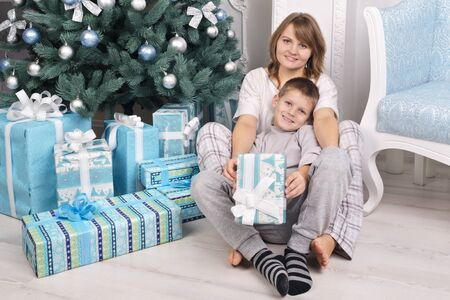 Mother and son happy gifts near a Christmas tree. Christmas scene. Looking at the camera Stock Photo