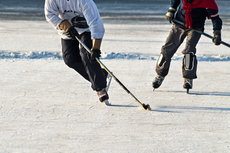 AFICIONADOS: Hockey player practising on a frozen pond outdoor. People playing amateur hockey. Winter playing, fun, snow.