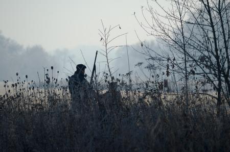 Silhouet van de twee jagers bij zonsopgang. Jagersman en -jongen tijdens de jachtperiode op zoek naar wilde vogels of wild. Herfst jachtseizoen. Grootvader leert zijn kleinzoon het jachtschip Stockfoto - 84055267