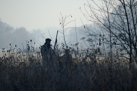 Silhouette of the two hunters at sunrise. Hunter man and boy during hunting period in search of wildfowl or game. Autumn hunting season. Grandfather teaches his grandson the hunting craft