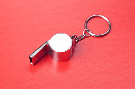 Sports or coaches metal whistle, closeup. Concept refereeing sport on red card background. Soccer or football referee whistle and caution cards Banque d'images
