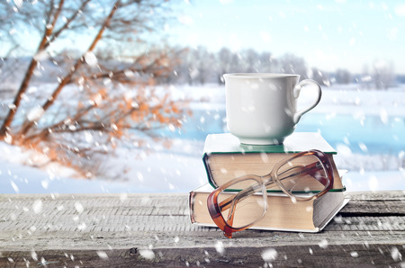 Hot coffee or tea, cocoa, chocolate cup on book and eyeglasses outdoors in winter. Pile of books, glasses and cup in nature.