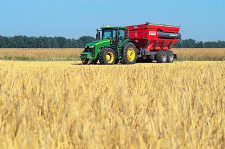 Kazanka, Ukraine - July 11: John Deere Tractor 8370R Tractor using a bunker-reloader Perard Interbene 27 harvesting grain in the field near the village Kazanka, South Ukraine July 11, 2017 Editorial