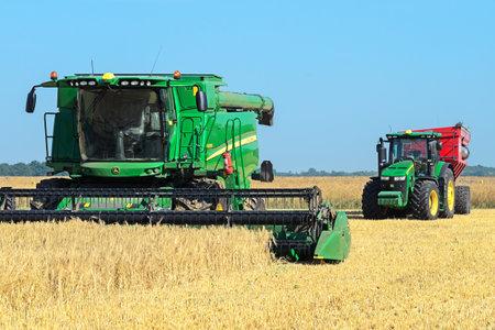 Kazanka, Ukraine - July 11: John Deere Combine Harvester T670 and Tractor 8370R Tractor using a bunker-reloader Perard Interbene 27 harvesting grain in the field near the village Kazanka, South Ukraine July 11, 2017