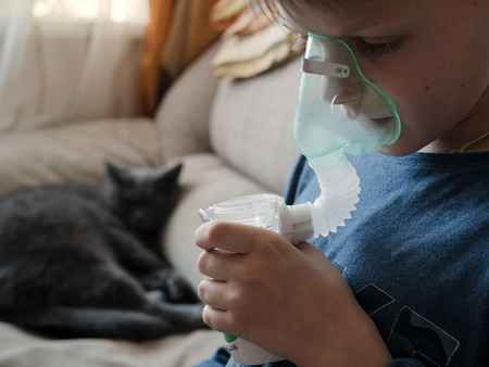 Young boy using nebulizer for asthma and respiratory diseases at home. Teenager doing inhalation inhales couples containing medication. Concept of home treatment. Medical procedures. Teen breathes with face mask of modern jet nebulizer.