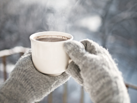 Woman hands in mittens holding a cozy steaming mug or cup with hot cocoa, tea or coffee. Beautiful girl enjoying winter morning or evening outdoors under snowfall. Winter and Christmas time concept Stock Photo