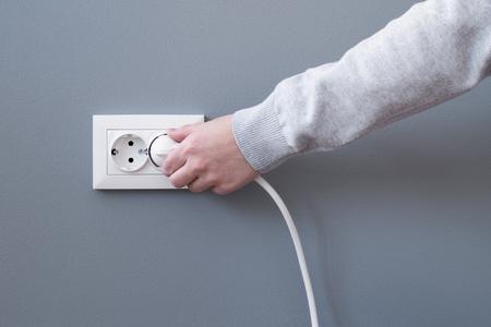 Enchufe a mano un cable eléctrico en un enchufe de plástico blanco o en un enchufe europeo en una pared de yeso gris. Primer plano de la mano de una mujer insertando un enchufe eléctrico en un enchufe de pared. Luz.