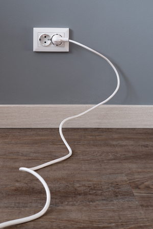 White power cord cable plugged into european wall outlet on grey plaster wall with copy space. European interior outlet socket with a plugged in cable. Daylight. Reklamní fotografie