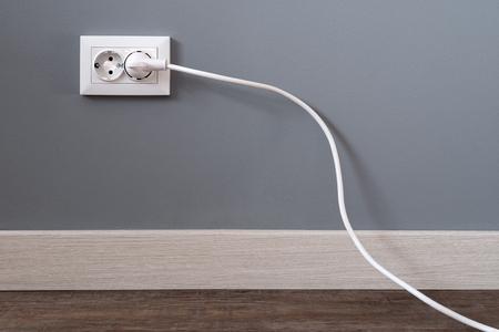 Cable de alimentación blanco enchufado a una toma de corriente europea en una pared de yeso gris con espacio de copia. Toma de corriente interior europea con un cable enchufado. Luz.