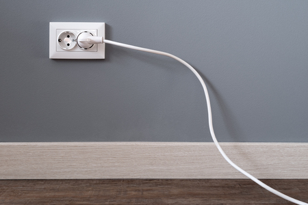 White power cord cable plugged into european wall outlet on grey plaster wall with copy space. European interior outlet socket with a plugged in cable. Daylight.