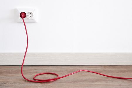 Cable de alimentación rojo enchufado a una toma de corriente europea en una pared de yeso blanco con espacio de copia. Toma de corriente interior europea con un cable rojo enchufado.