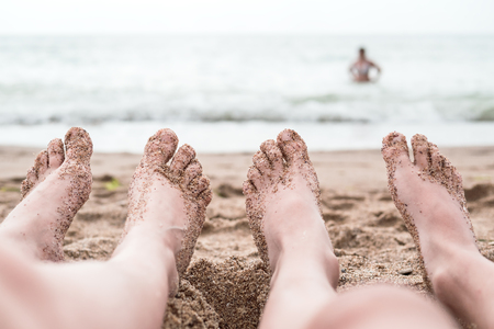 Womans or men feet on the coarse sand near the sea. Relaxation at sea in countries with cold climates. Beach vacation holidays concept of freedom and travel. Close-up. Copy space. Travel lifestyle.