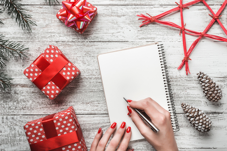 A modern white background of a white background card, and a young lady who writes a message for the new year with a white sheet for the message, a new greeting card, red star and christmas magic
