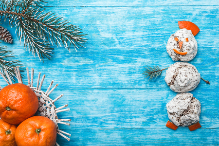 Azure wood background. Green fir tree. Decorative cones. Snowman from sweets. Fruit with mandarin. Space for Christmas or New Year Message. Xmas and Happy New Year composition. Flat lay, top view