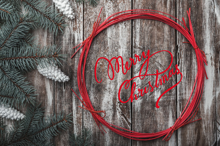 Old wooden background. Green fir branches. White cones. Red decorative circle. Space for message Xmas, Christmas and New Year. Letter to Santa. Xmas and Happy New Year composition. Flat lay, top view. Stock Photo