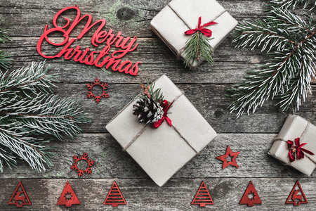 Upper, top, view from above of winter figurines, evergreen branch, present boxes and red Merry Christmas inscription on gray background, with space for text writing, greeting. Stock Photo