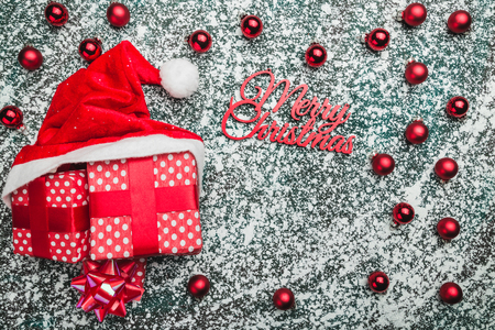 Upper, top, view from above of, evergreen red toys, Christmas presents and Santa hat on gray marble background, with space for text writing, greeting. Stock Photo