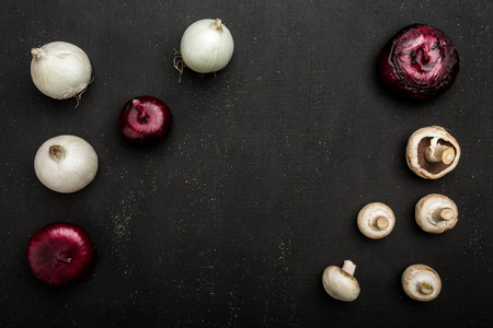 Composition of mushrooms and onion on black background, top view