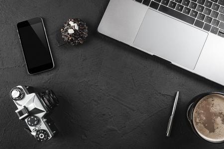 Mesa de escritorio de fotógrafo negro con cámara de película, computadora portátil, teléfono y café. Vista superior con espacio de copia, endecha plana