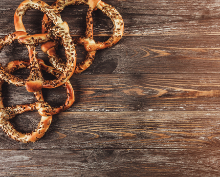 Freshly baked homemade pretzels with seeds on rustic wooden table. Top view, light effect 免版税图像