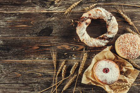 Tasty donuts with jam and pretzel on old wooden background. Vintage concept, flat lay and copy space 免版税图像