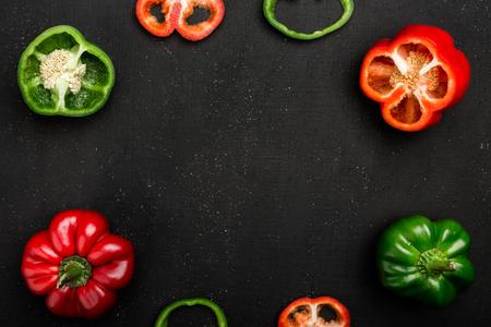 Pimientos morrones rojos y verdes o pimientos dulces o pimientos enteros, cortados por la mitad y en rodajas sobre tabla oscura. Verduras frescas, espacio de copia