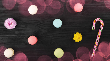 Sweet macarons on wooden table, flowers and lollipop. Top view with colored bokeh lights effects Stock Photo