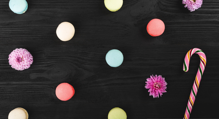 Holiday concept, variety of macarons and flowers on wooden black background. Top view Stock Photo