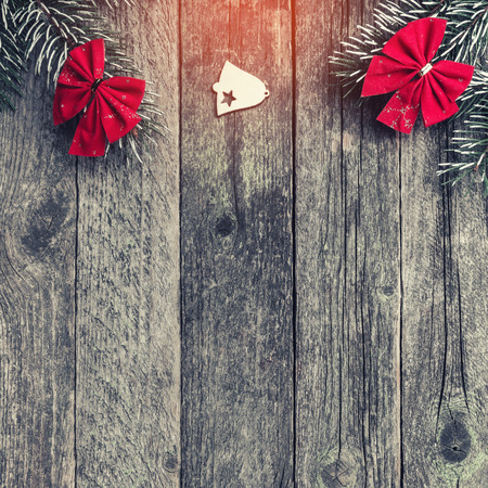 Fir branches with red bows, and xmas handmade toys on wooden gray background, with space for text, Christmas greeting card