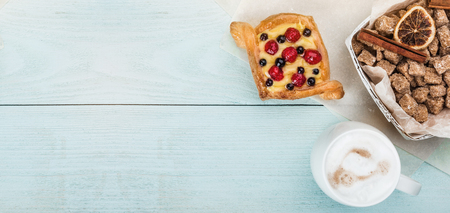Delicious pastry with berries and cream for breakfast on wooden blue background, top view Stockfoto