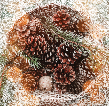 Above, top, flat view on a basket with fir, evergreen tree, pines, cones, on stone, marble, background, Xmas greeting card.