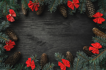 Xmas greeting card. Row of fir branches with cones and red bowls, on black wooden background. Top view Standard-Bild