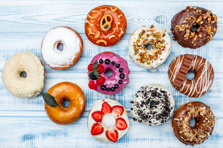 Assortment of donuts for any taste, on old wood background.