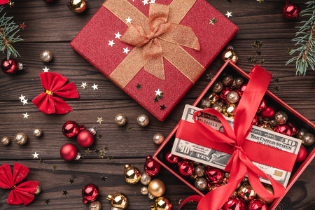 A Christmas gift, money packed with red slack, Xmas items, on a wooden background. Top view.