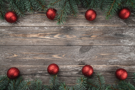 Old wood background with fir branches adorned with baubles. Space for text. Christmas card. Top view. Xmas. Stock Photo