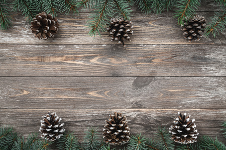 Old wooden background with fir branches adorned with cones. Space for text. Christmas card. Top view. Xmas.