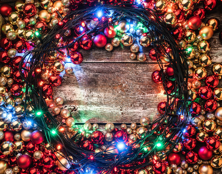Christmas background with red and gold baubles, lighted around, in the center of space for your message. Top view. Xmas congratulations.