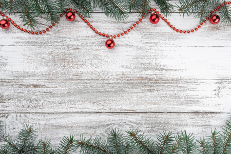 Xmas card. Old wooden Christmas background. Fir branches. Red baubles and garlands. Top view. Space for your text.