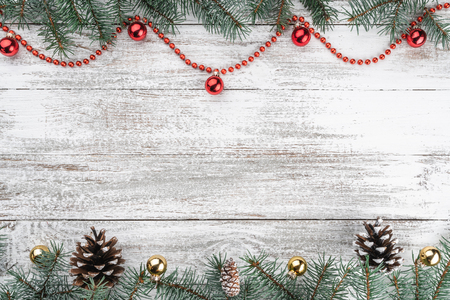 Old wooden Christmas background. Fir branches and cones. Gold and red baubles and garlands. Top view. Space for your text. Xmas card.