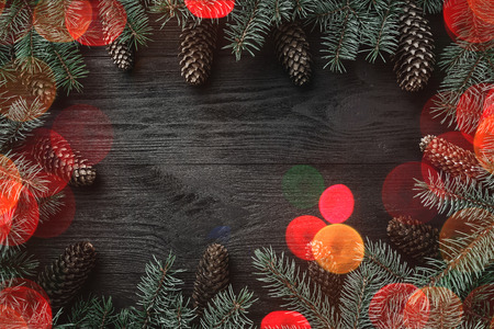 Black wood background, with fir branches around the edges, and cones. Top view. Xmas greeting card with light bulb effect.