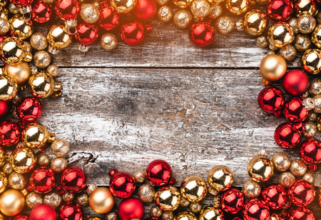 Old wooden background. Frame of red and gold baubles. Top view. Stock Photo