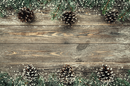 Old wooden background with fir branches adorned with cones. Space for text. Christmas card. Top view. Xmas. Snow effect. Banco de Imagens